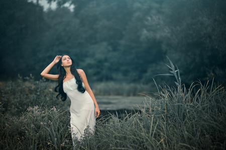 Beautiful but sad woman in fairytale, wood nymph among tall grass and rays of light. Outdoor. Stok Fotoğraf