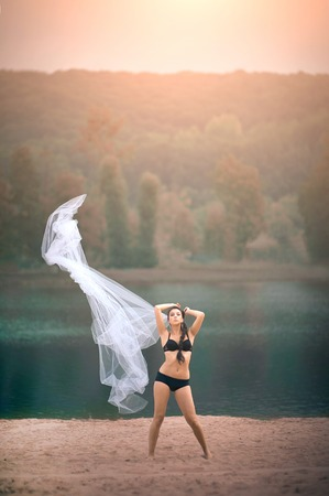 Young sexy woman in underwear on beach at summer day with large veil.