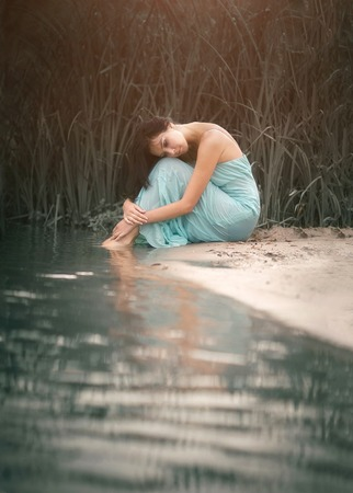 Charming and romantic girl sleeping and dreams near the water stream. Outdoor. Stok Fotoğraf