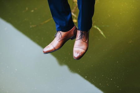 Legs and boots of a young man over the lake with reflection