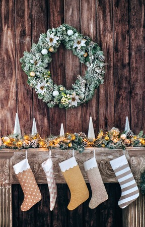 Christmas socks on decorated fireplace, background of a wooden wall with a green wreath. Stok Fotoğraf