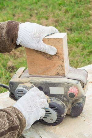 ?arpenter works with belt sander  and processes a wooden block in the forest