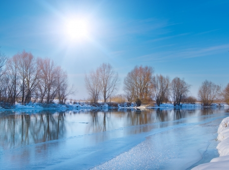 swedish: snow-covered winter river in sunny day