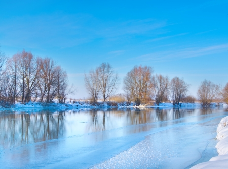 snow-covered winter river in sunny day photo