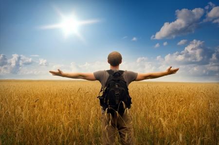 Giovane uomo in piedi su un campo di grano su sfondo cielo al tramonto Archivio Fotografico - 15828665