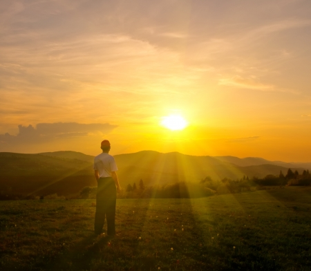 the rising sun: hombre joven en el césped verde en las montañas al atardecer