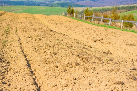 Brown soil of an agricultural field in the mountains photo