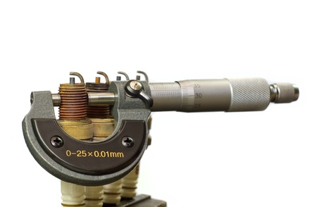 micrometer: A micrometer and spark plugs Stock Photo