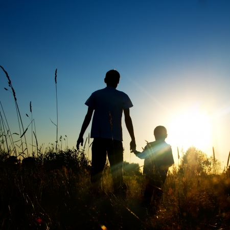 Silhouette father and son at sunset  photo