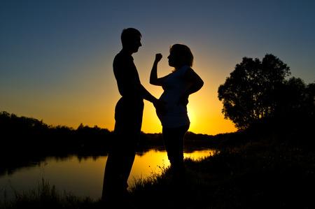abusing: Mujer joven embarazada que abusa de su marido en la orilla del r�o al atardecer