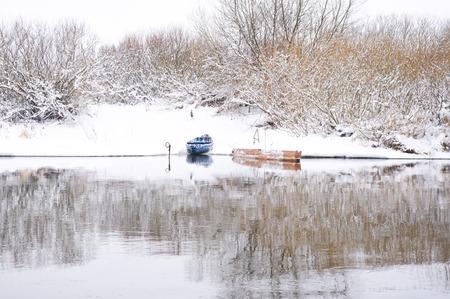 Boats on shore of winter river Archivio Fotografico - 96392704