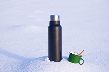 flask and mug in the snow Archivio Fotografico - 96451395
