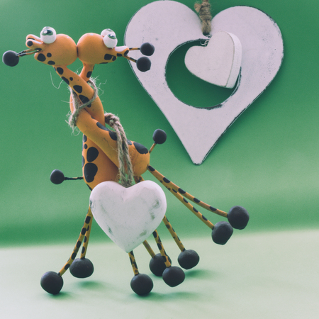 A small statue in the shape of yellow giraffes. They hug each other by the neck and finally give a kiss, on a green background and a white heart. Stok Fotoğraf
