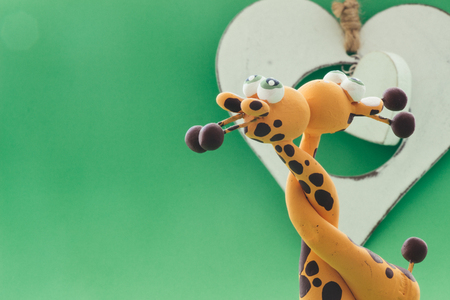 A small statue in the shape of yellow giraffes. They hug each other by the neck and finally give a kiss, on a green background and a white heart. Stock Photo