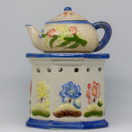 A particular ceramic candlestick made of three pieces. Floral-themed work in blue, red, yellow colors.