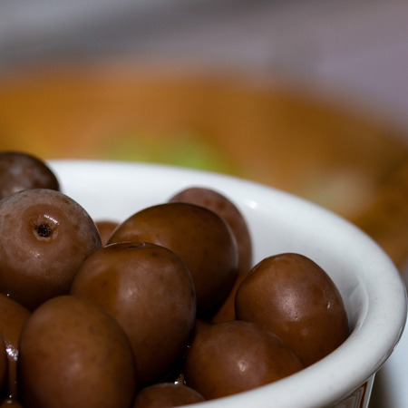 Typical food for an aperitif of Italian cuisine. Olives served inside a white ceramic bowl. Stock Photo