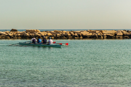 Workouts on a morning of May on the sea of Bari, in southern Italy. Four men on rowing.