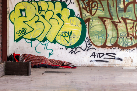 A homeless man sleeps inside a sleeping bag, with his feet uncovered, on the floor of a desolate city street, marked by some graffiti.