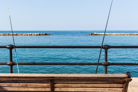 Bari, Italy - 04 21 2018: Two fishing rods fixed between a wooden bench and an iron railing, on the waterfront of the city of Bari, in south of Italy.