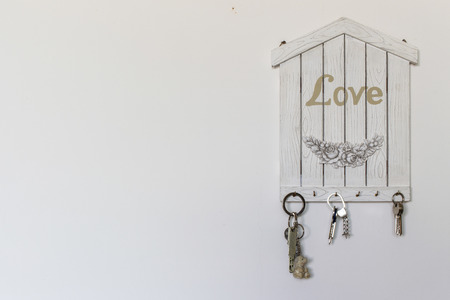 Decorations and objects for interiors. A keychain in the shape of a house as a concept of love and family. Фото со стока - 116021028