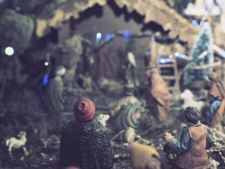 Christmas holidays at home. A christmas nativity scene with lights and small wooden statues illuminates the living room during the evening. Archivio Fotografico