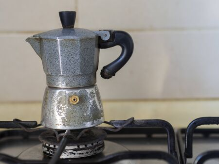 As it starts every morning for most Italians. An old coffeepot on an oven in the kitchen on the background of the white wall of the house. Reklamní fotografie
