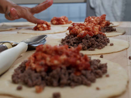 Preparations for a panzerotto, a specialty of southern Italian cuisine. Minced meat, mozzarella and tomato poured as a filling on the dough. 版權商用圖片