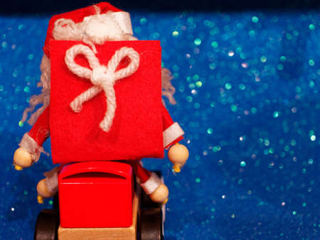 Decorations to furnish the house during the month of December. A felt Santa Claus carries presents on top of a wooden car. Archivio Fotografico