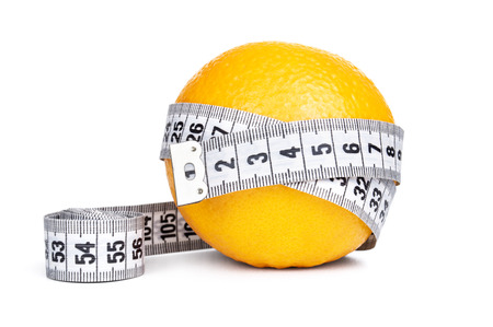 Orange fruit with tape measure on white background photo