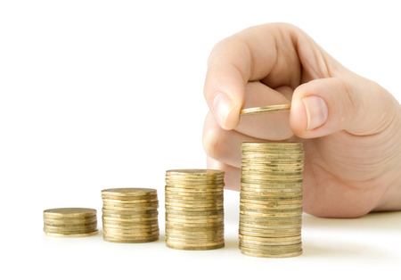 man holding money: coins in finger and row stacks them isolated on white Stock Photo