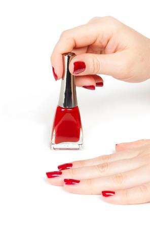 acrylic nails: woman applying red nail polish
