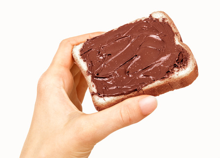 spreaded: baguette slice spread with nut-choco paste in man hand, isolated on white Stock Photo