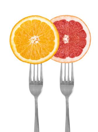 citrus fruit on forks, orange, grapefruit, isolated against white photo