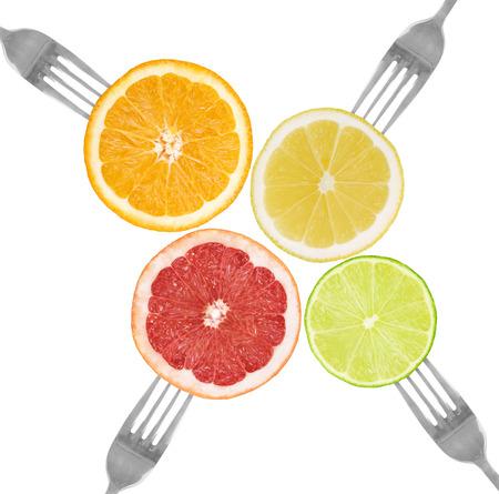 citrus fruit on forks lime, orange, grapefruit, lemon isolated against white photo