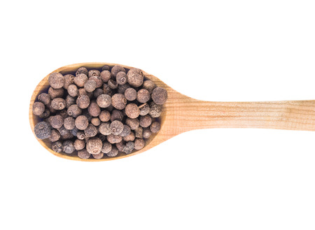 black pepper in wooden spoon on white background photo