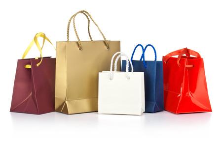 Geassorteerde boodschappentassen met inbegrip van rood, goud, blauw op een witte achtergrond Stockfoto