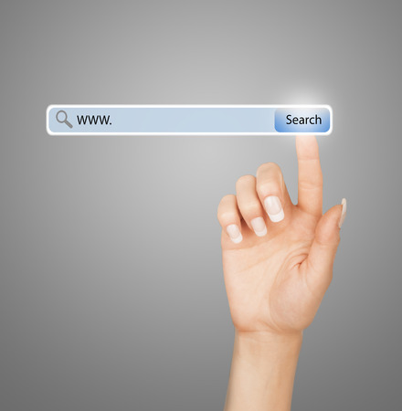 technology, searching system and internet concept - woman hand pressing Search button photo