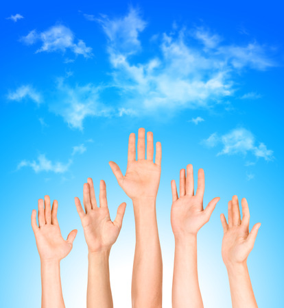 many open hands raised up against the sky,business concept photo