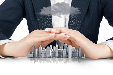 Female hands saving small city with a roof