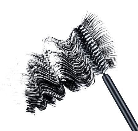 smear of black brush mascara and false eyelashes isolated on white background photo