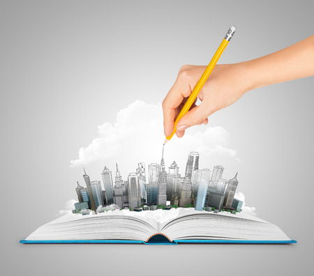 Hand drawing a city on an open book Stok Fotoğraf