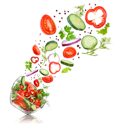 glass salad bowl in flight with vegetables: tomato, pepper, cucumber, onion, dill and parsley. Isolated on white background Foto de archivo