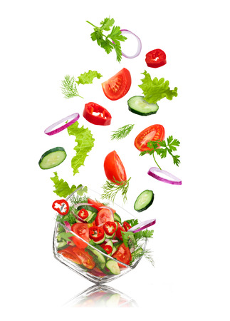 glass salad bowl in flight with vegetables: tomato, pepper, cucumber, onion, dill and parsley. Isolated on white background Imagens