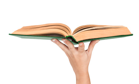 Female hand holding an open vintage book in green cover photo