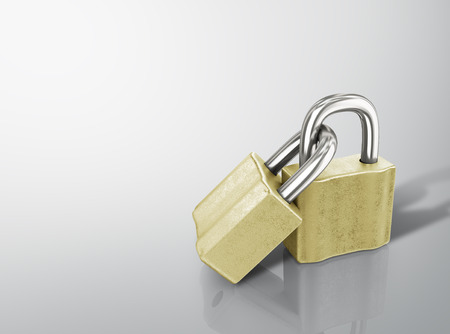 Two linked gold padlocks with reflections on a white background photo