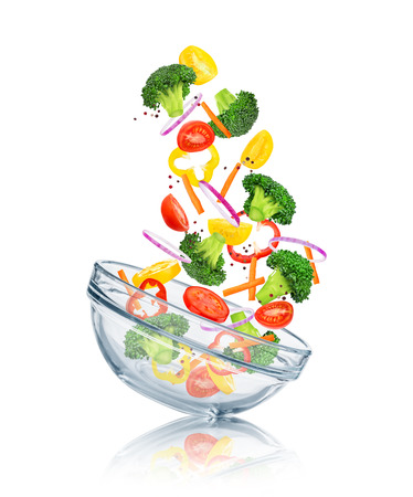 vegetables falling into a glass bowl on a white background. Concept slim figure