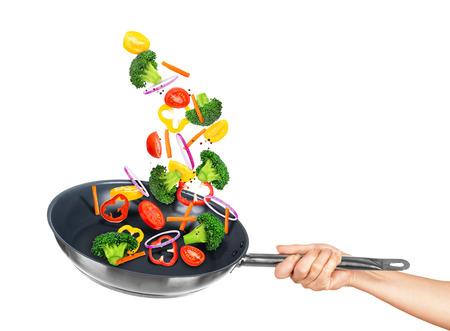 Vallende groenten in de pan op een geïsoleerde witte achtergrond