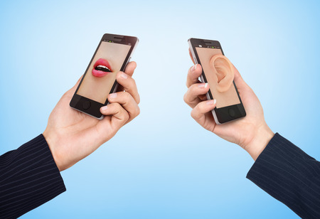 mouth screen: Phone cell concept. Mans hand holding phone with speaking womans mouth in display and woman hand holding phone with ear in the screen.