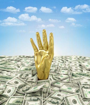 Gold hand makes its way through a bunch of dollars. photo