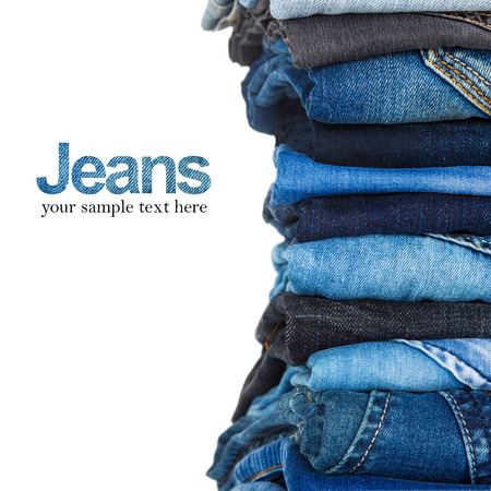 mezclilla: pila de distintos tonos de jeans azul sobre fondo blanco Foto de archivo